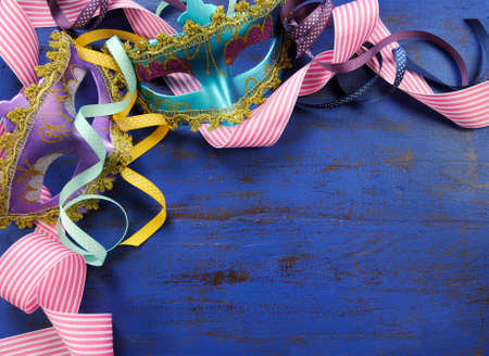 masquerade masks: Happy New Year background with pink, purple and blue masquerade party masks and decorations on dark blue rustic distressed vintage wood.