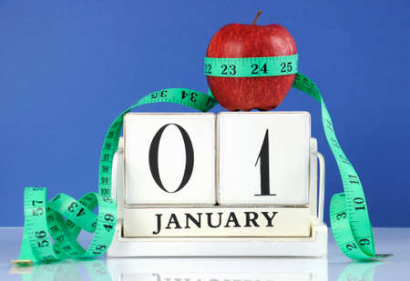Happy New Year healthy slimming weight loss or good health resolution with red apple and measuring tape on white wood vintage style calendar for January first.