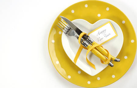 31: Bright and modern yellow and white theme Happy New Year table with heart shape plate on polka dot place setting, with copy space.