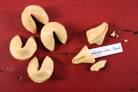 Happy New Year message greeting inside Chinese New Year fortune cookie on red recycled wood background.