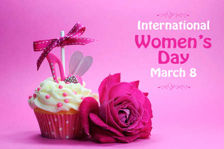 Happy International Womens Day greeting with pink rose and cupcake with high heel shoe on pink background with sample text.