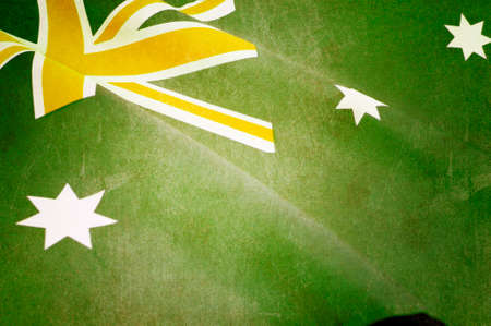 australia day: Retro grunge style background close up of Australian Southern Cross flag for national public holiday event in unofficial green and gold colours. Stock Photo