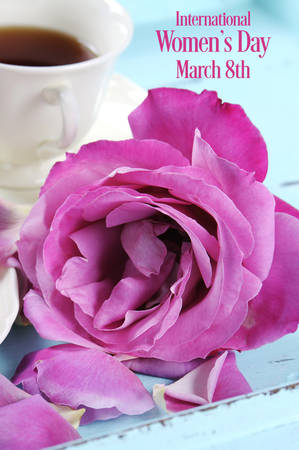 sample text: Happy International Womens Day greeting with pink rose and afternoon tea tray on pink background with sample text.