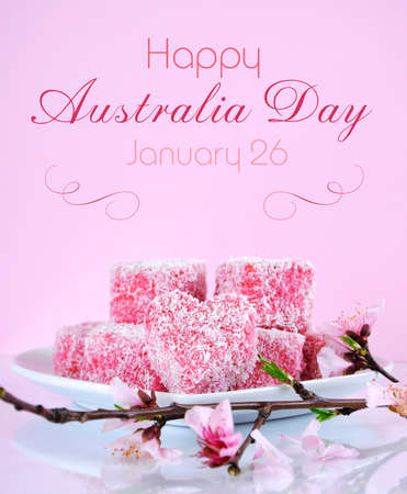 australia day: Homemade Australian style pink heart shape small lamington cakes with spring blossom on a reflective table against a pink background with Happy Australia Day greeting sample text.