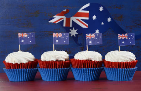 australia flag: Happy Australia Day January 26 party food with red velvet cupcakes with kangaroo flag on dark red and blue vintage rustic recycled wood background.