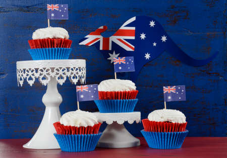 downunder: Happy Australia Day January 26 party food with red velvet cupcakes with kangaroo flag on dark red and blue vintage rustic recycled wood background.