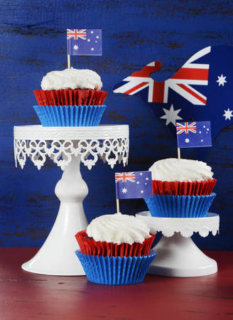 party with food: Happy Australia Day January 26 party food with red velvet cupcakes with kangaroo flag on dark red and blue vintage rustic recycled wood background.