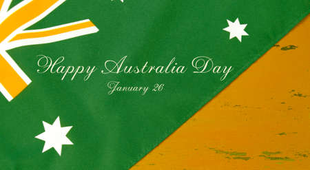 downunder: Australian flag in unofficial green and gold colours on yellow recycled wood background with sample text for Happy Australia Day.