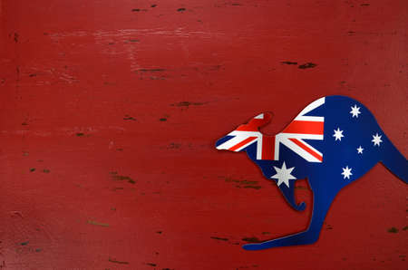 downunder: Australia Day background with kangaroo shape Australian flag on red rustic recycled wood background.