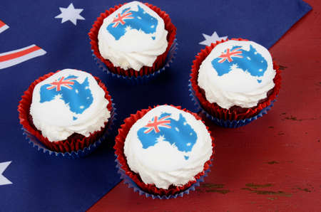 party with food: Happy Australia Day January 26 party food with red velvet cupcakes and Australian maps rice paper toppers on dark red and blue vintage rustic recycled wood background.