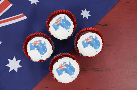 downunder: Happy Australia Day January 26 party food with red velvet cupcakes and Australian maps rice paper toppers on dark red and blue vintage rustic recycled wood background.