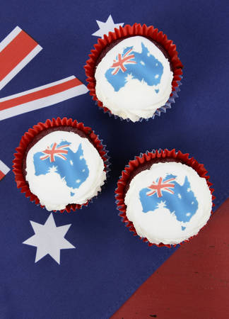 Happy Australia Day January 26 party food with red velvet cupcakes and Australian maps rice paper toppers on dark red and blue vintage rustic recycled wood background. photo