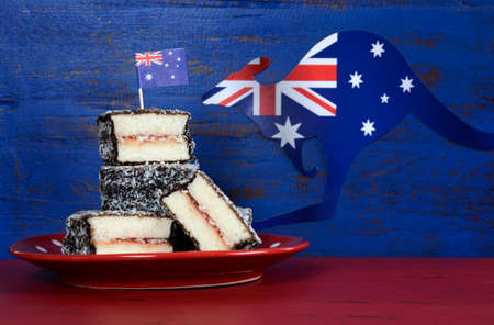downunder: Happy Australia Day January 26 party food with iconic Australian lamington cakes on dark red and blue vintage rustic recycled wood background.