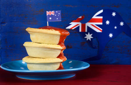 downunder: Happy Australia Day January 26 party food with iconic meat pies and tomato sauce on dark red and blue vintage rustic recycled wood background. Stock Photo