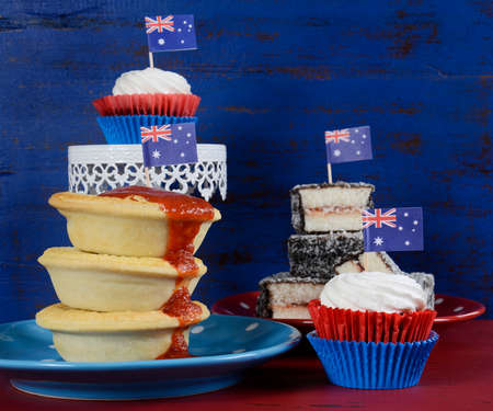 downunder: Happy Australia Day January 26 party food with iconic meat pies, lamingtons and cupcakes on dark red and blue vintage rustic recycled wood background. Stock Photo