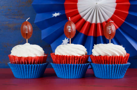 playoffs: Red, white and blue theme cupcakes with football toppers for Super Bowl Sunday party or collage football finals and playoffs.