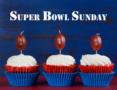 super bowl: Red, white and blue theme cupcakes with football toppers for Super Bowl Sunday party or collage football finals and playoffs, with sample text greeting. Stock Photo