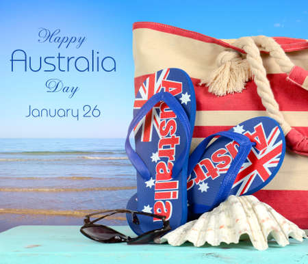 australian beach: Happy Australia Day, January 26, theme white wood vintage calendar and red, white and blue cupcakes with view of Australian beach background.
