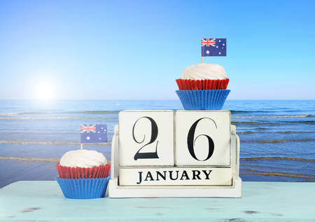 australia day: Happy Australia Day, January 26, theme white wood vintage calendar and red, white and blue cupcakes with view of Australian beach background.