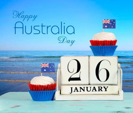 australian beach: Happy Australia Day, January 26, theme white wood vintage calendar and red, white and blue cupcakes with view of Australian beach background, with sample text greeting message. Stock Photo