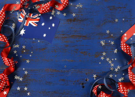 Happy Australia Day, January 26, theme dark blue vintage distressed wood background with Australian flag and decorations with copy space for your text here. Imagens