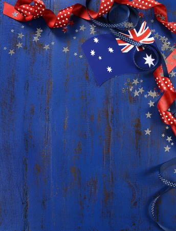 Happy Australia Day, January 26, theme dark blue vintage distressed wood background with Australian flag and decorations with copy space for your text here, vertical.
