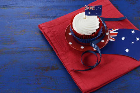 Happy Australia Day, January 26, theme table setting with red, white and blue cupcake on red polka dot plate and Australian flag decoration on dark blue wood background.