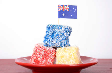 australian flag: Happy Australia Day red, white and blue lamingtons party food on red wood table against white background.