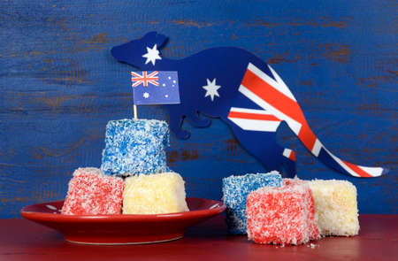 tucker: Happy Australia Day red, white and blue lamingtons on red and blue dark recycled wood background.