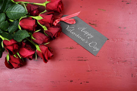 february 14: Happy Valentines Day background with red roses with greeting card on distressed vintage recycled wood table.