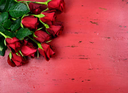 Happy Valentines Day background with red roses on distressed vintage recycled wood table. photo