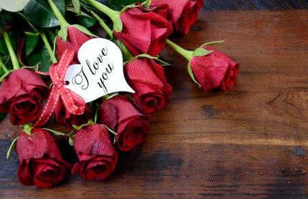 and bouquet: Happy Valentine Rose rosse sul tavolo di legno scuro. Archivio Fotografico