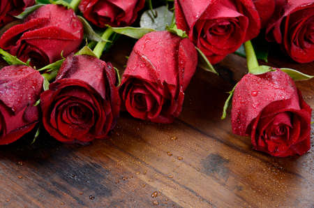 Happy Valentine Red Roses on dark wood table. photo