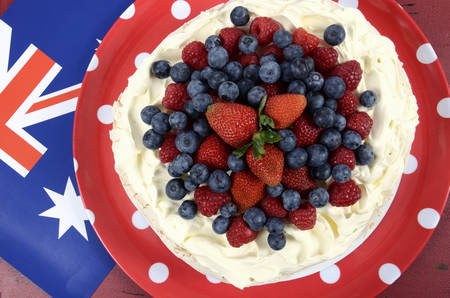 above 25: Australian traditional dessert, Pavlova, with whipped cream and strawberries, blueberries and raspberries in red white and blue theme with Australian flag. Overhead. Stock Photo