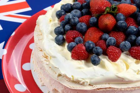 tucker: Australian traditional dessert, Pavlova, with whipped cream and strawberries, blueberries and raspberries in red white and blue theme with Australian flag.