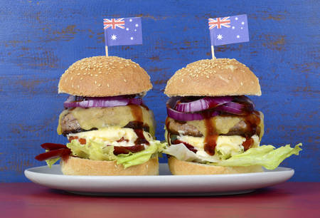 barbeque: The Great Aussie BBQ Burger - with barbeque beef burgers and salad piled high with Australian flag against a red and blue distressed wood background.