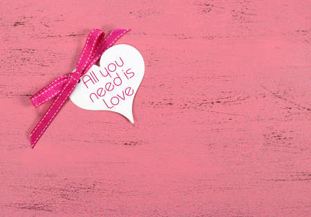 Valentine greeting heart shape gift tag with All You Need Is Love sample text on pink wood table. photo