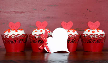 red velvet: Happy Valentine red velvet cupcakes with love messages on red vintage wood background, with greeting card. Stock Photo