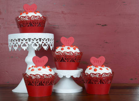 red velvet: Happy Valentine red velvet cupcakes with love messages on red vintage wood background.