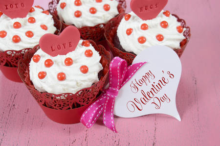 Happy Valentine red velvet cupcakes with love messages on pink vintage wood background with greeting card. photo