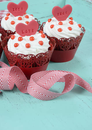 Happy Valentine red velvet cupcakes with love messages on green teal blue sixties style vintage wood background. photo