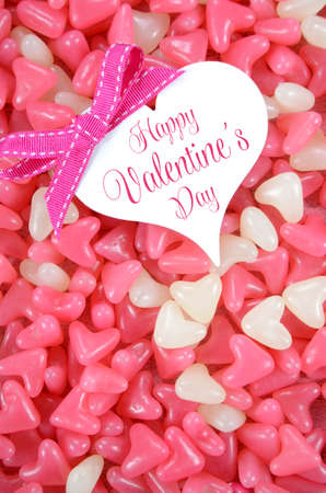 confectionary: Valentines Day pink and white heart shape jelly candy confectionary on pink wood background with heart greeting card and sample text - vertical.