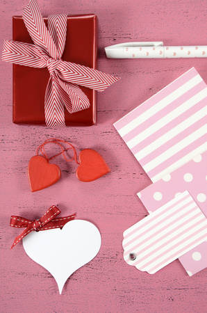 Wrapping Happy Valentines Day gifts with gift tags and hearts on shabby chic pink background - vertical. photo