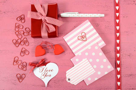 Wrapping Happy Valentines Day gifts with gift tags and hearts on shabby chic pink background. photo