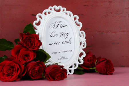 Happy Valentines Day romantic vintage style white photo frame against red and pink rustic wood background with bouquet of red roses, with A True Love Story Never Ends sample text. photo