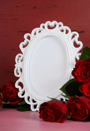 Happy Valentines Day romantic vintage style white photo frame against red and pink rustic wood background with bouquet of red roses, vertical with copy space for your text here. photo