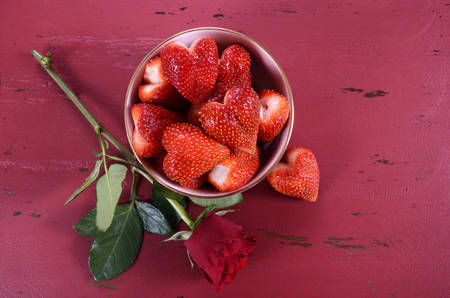 february 14: Happy Valentines Day bowl of luscious heart shape red strawberries on a red vintage wood background, with copy space. Stock Photo