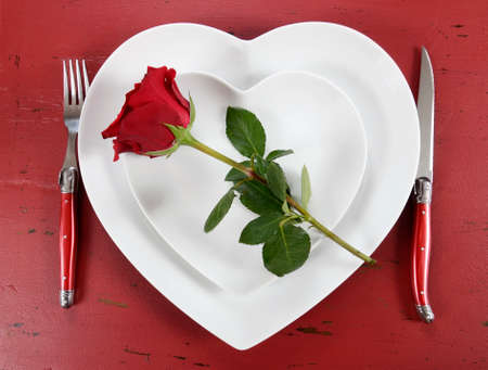 Happy Valentines Day table place setting on red vintage wood background with red rose, overhead. photo