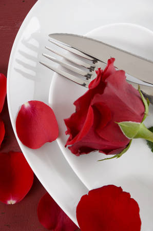 Happy Valentines Day table place setting on red vintage wood background with red rose, vertical. closeup overhead. photo