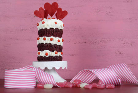 red velvet cupcake: Novelty triple layer red velvet cupcake on white cake stand with ribbons and candy against a vintage shabby chic pink and red wood background. Stock Photo